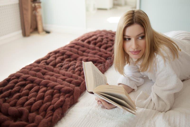 L?sa i underlag Ung härlig blond flicka som ligger på sängen och läser en bok Hobby och att koppla av fotografering för bildbyråer
