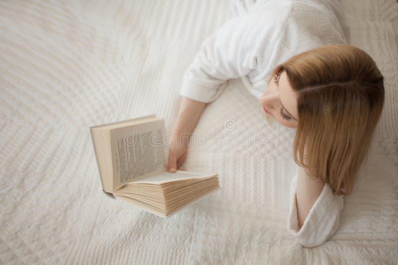 L?sa i underlag Ung h?rlig blond flicka som ligger p? s?ngen och l?ser en bok Hobby och att koppla av royaltyfri bild