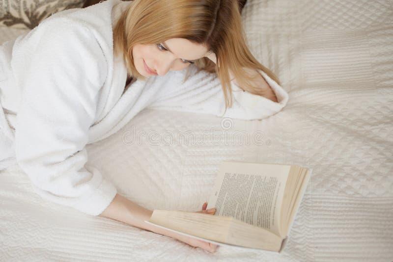 L?sa i underlag Ung h?rlig blond flicka som ligger p? s?ngen och l?ser en bok Hobby och att koppla av arkivfoton