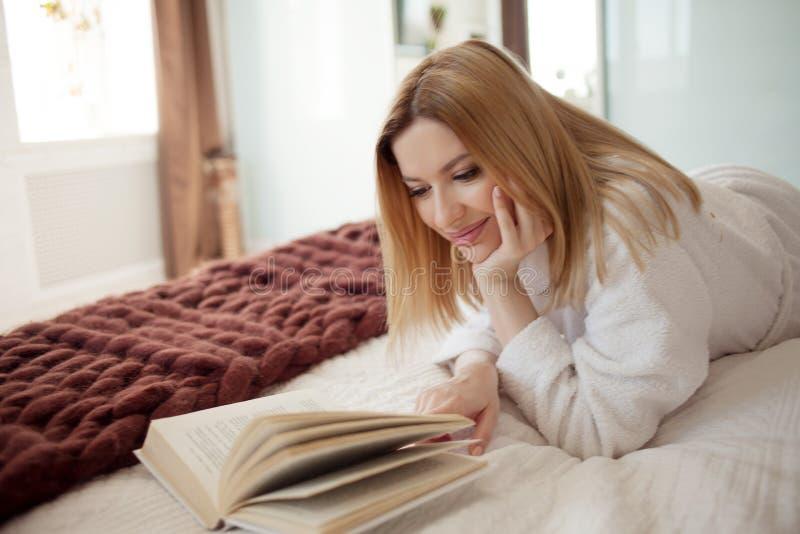 L?sa i underlag Ung h?rlig blond flicka som ligger p? s?ngen och l?ser en bok Hobby och att koppla av royaltyfri fotografi