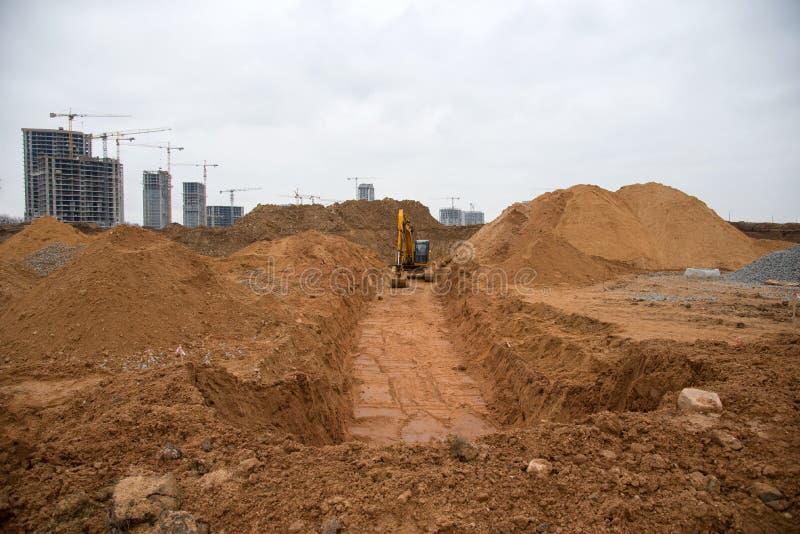 L'scavatore estrae una grande fossa per la posa di tubi Backhoe durante il movimento a terra nel cantiere Apparecchiature pesanti fotografie stock libere da diritti