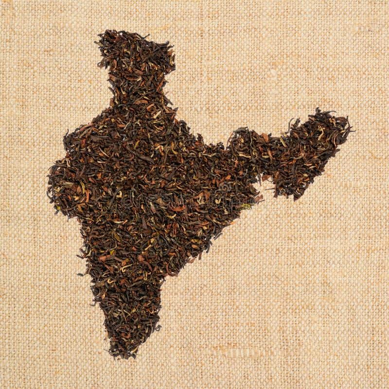 L?sen Sie schwarzen Tee Die Kontur des Indiens wird von Inder-Assam-Tee auf schlichtem Leinensegeltuchhintergrund gemacht stockfotos