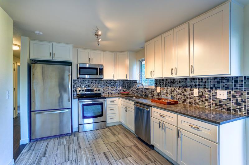 L-shape kitchen room design. With white cabinets, brown granite countertops, mosaic backsplash, built in stainless steel appliances and wide plank hardwood royalty free stock photo