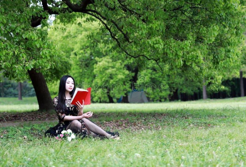 l?st sittande tree f?r blomning bok under arkivfoto