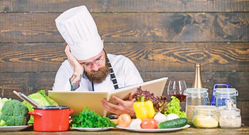 L?ste den sk?ggiga hipsteren f?r mannen bokrecept n?ra nya gr?nsaker f?r tabellen kulinariska konster Recept som lagar mat sund m arkivfoton