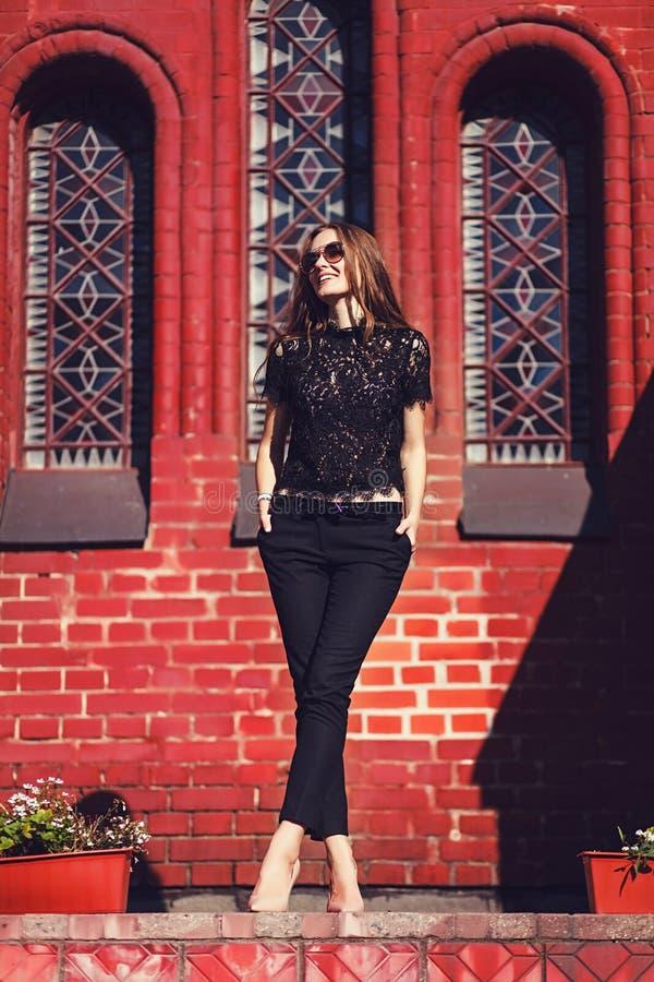 L stilfull flicka som går och poserar i svart kläder arkivbild