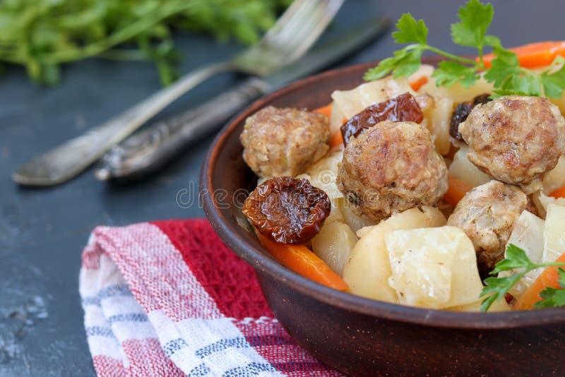 L?t sm?koka potatisar med k?ttbullar, mor?tter och sol-torkade tomater i en bunke mot en m?rk bakgrund arkivbilder