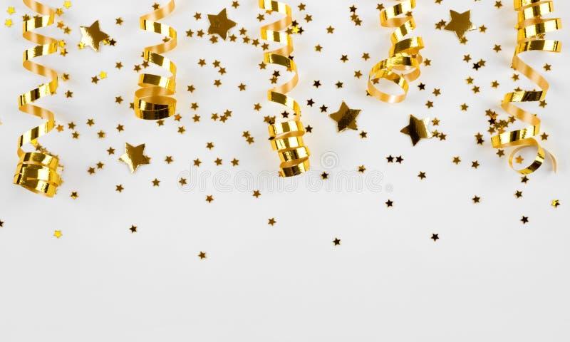 L'or tient le premier rôle des confettis et des rubans courbés d'isolement sur le fond blanc images libres de droits