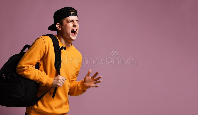 L'?tudiant joyeux de jeune homme avec un sac ? dos court dans le studio sur un fond pourpre images libres de droits