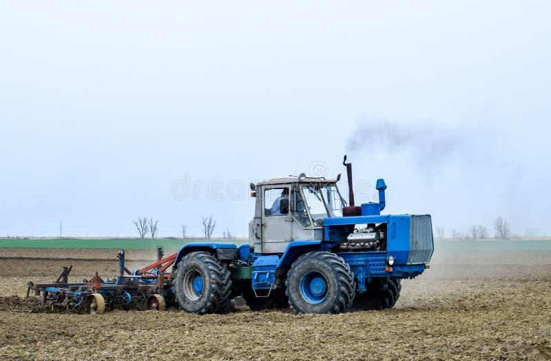 L'ubriacone ed allenta il suolo sul campo prima della semina Il trattore ara un campo con la a immagini stock libere da diritti