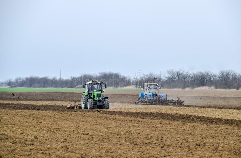 L'ubriacone ed allenta il suolo sul campo prima della semina Il trattore ara un campo con la a immagini stock