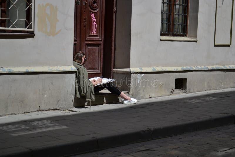 L'UCRAINA, Leopoli-luglio 30,2015: Una ragazza sta facendo gli schizzi di una città che si siede sulla via di Wirmen fotografie stock libere da diritti