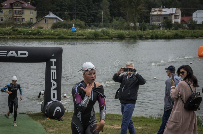 L'UCRAINA, LEOPOLI - SETTEMBRE 2018: Un atleta esaurisce l'acqua in un idro-vestito dopo una nuotata durante la concorrenza di tr immagini stock