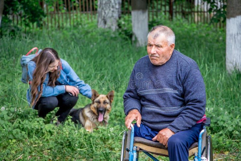 l'ucraina Regione di Khmelnitsky Maggio 2018 Un uomo anziano nel wheelc immagini stock libere da diritti