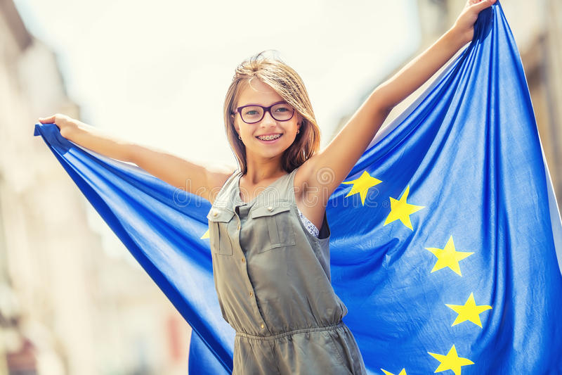 L'UE diminuent Fille heureuse mignonne avec le drapeau de l'Union européenne Jeune adolescente ondulant avec le drapeau d'Union e photos libres de droits