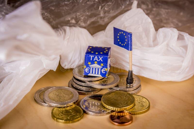 L'UE tracent avec d'euro pièces de monnaie et un sachet en plastique symbolisant le règlement fiscal en plastique européen image libre de droits