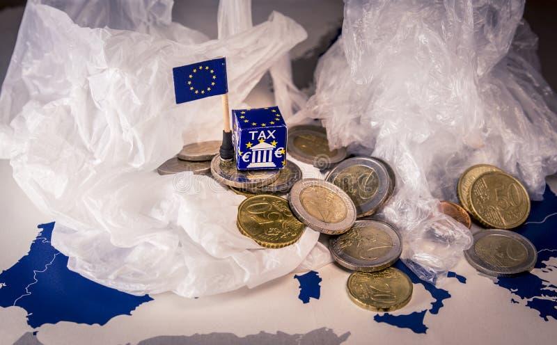 L'UE tracent avec d'euro pièces de monnaie et un sachet en plastique symbolisant le règlement fiscal en plastique européen photos stock