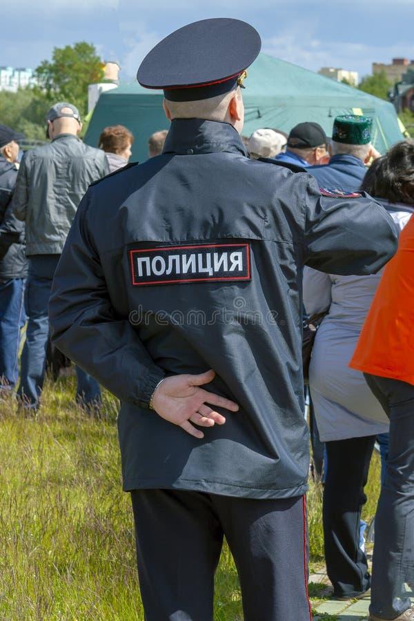 L'ufficiale di polizia maschio si occupa dell'ordine pubblico in vacanza, retrovisione fotografia stock