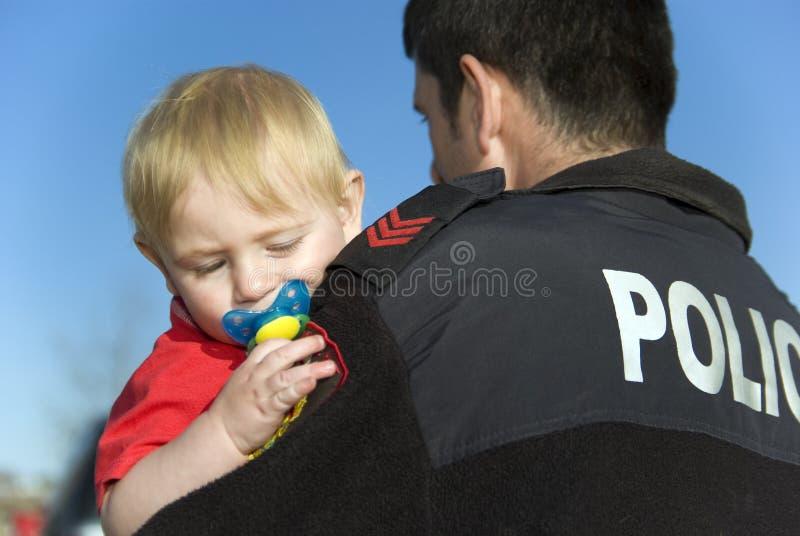 L'ufficiale di polizia tiene il bambino fotografia stock