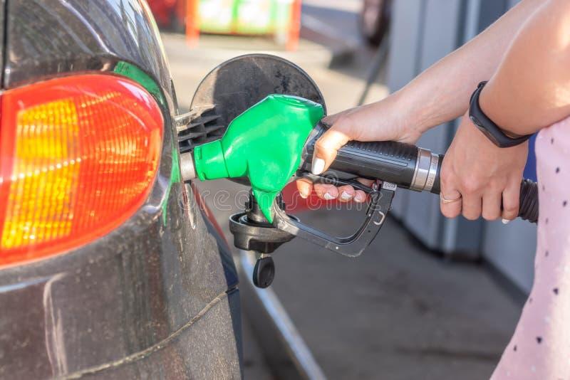 L'ugello della pompa di gas nel serbatoio di combustibile dell'automobile bronzea, rifornisce di carburante il petrolio al veicol fotografia stock