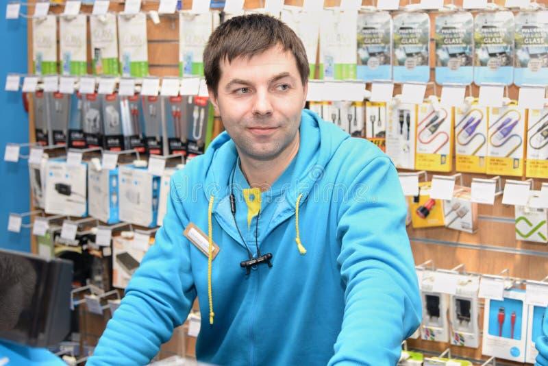 L'Ukraine, Shostka - 8 mars 2019 : Le consultant en matière de vendeur se tient derrière le compteur de magasin images stock