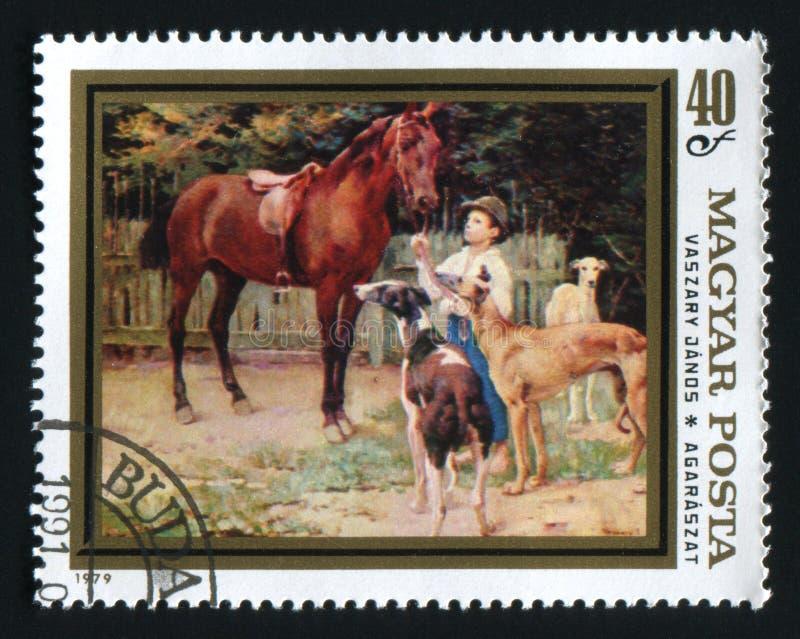 L'UNGHERIA - CIRCA 1979: Un bollo stampato in Ungheria mostra il bambino con il cavallo ed i levrieri da Janos Vaszary, circa 197 fotografia stock libera da diritti