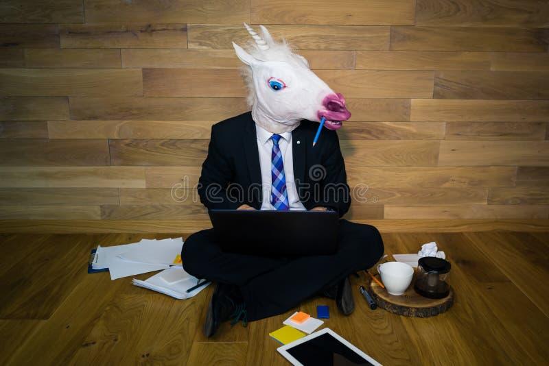 L'unicorno serio in un vestito ed in un legame funziona entusiasta a casa con la tazza di caffè sul supporto di legno immagine stock