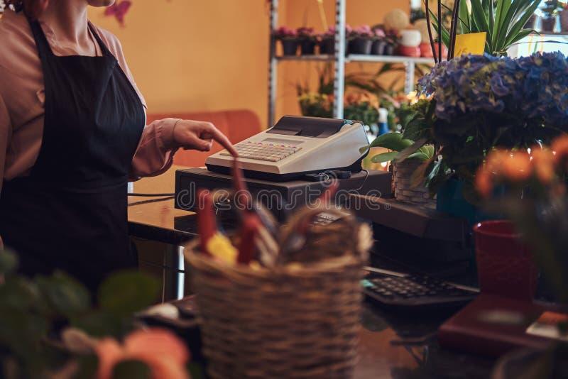 L'uniforme de port de fleuriste féminin roux avec du charme fonctionne avec la caisse enregistreuse dans le fleuriste images stock