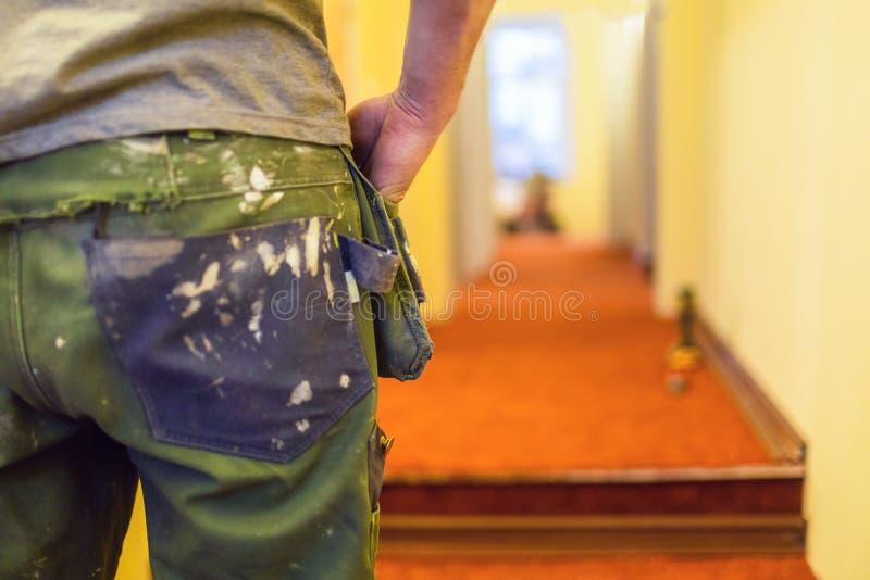 L'uniforme ou le boilersuit sale en peinture blanche - la robe fonctionnante du travailleur dans la maison est en construction, t photographie stock