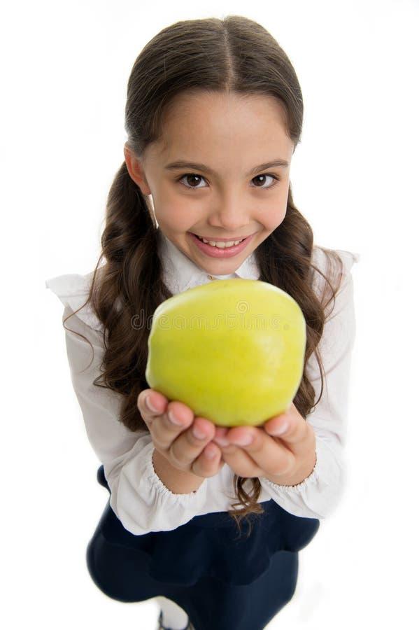 L'uniforme scolaire de fille d'enfant vêtx la pomme d'offres Le visage de sourire d'enfant futé d'enfant choisissent le casse-cro photos libres de droits