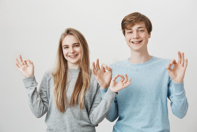 L'unità della famiglia assomiglia a questa Fratelli germani amichevoli affascinanti che sorridono largamente, stanti vicini e mos fotografie stock
