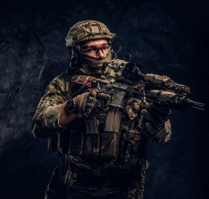 L'unité d'élite, soldat de forces spéciales dans l'uniforme de camouflage tenant un fusil d'assaut avec un laser aperçoivent et v photographie stock