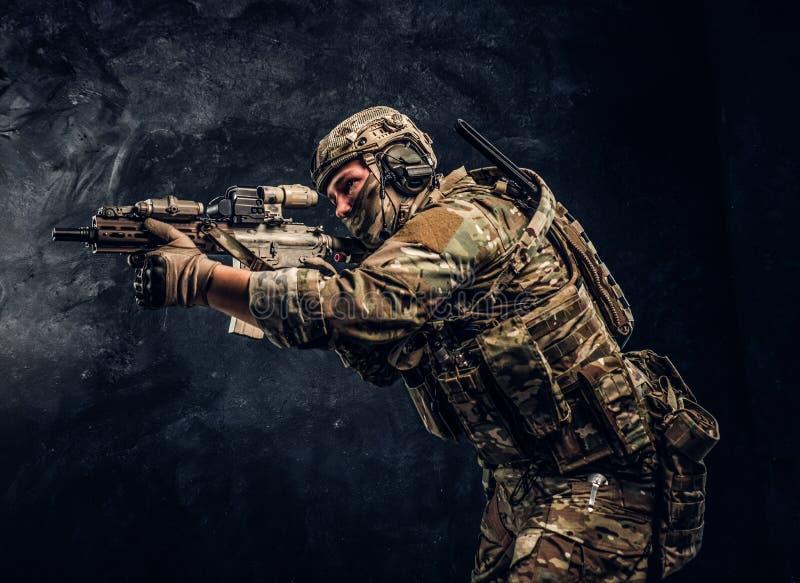 L'unité d'élite, soldat de forces spéciales dans l'uniforme de camouflage tenant un fusil d'assaut avec un laser aperçoivent et v images libres de droits