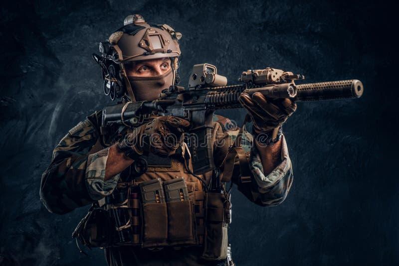 L'unité d'élite, soldat de forces spéciales dans l'uniforme de camouflage tenant un fusil d'assaut avec un laser aperçoivent et v photographie stock libre de droits