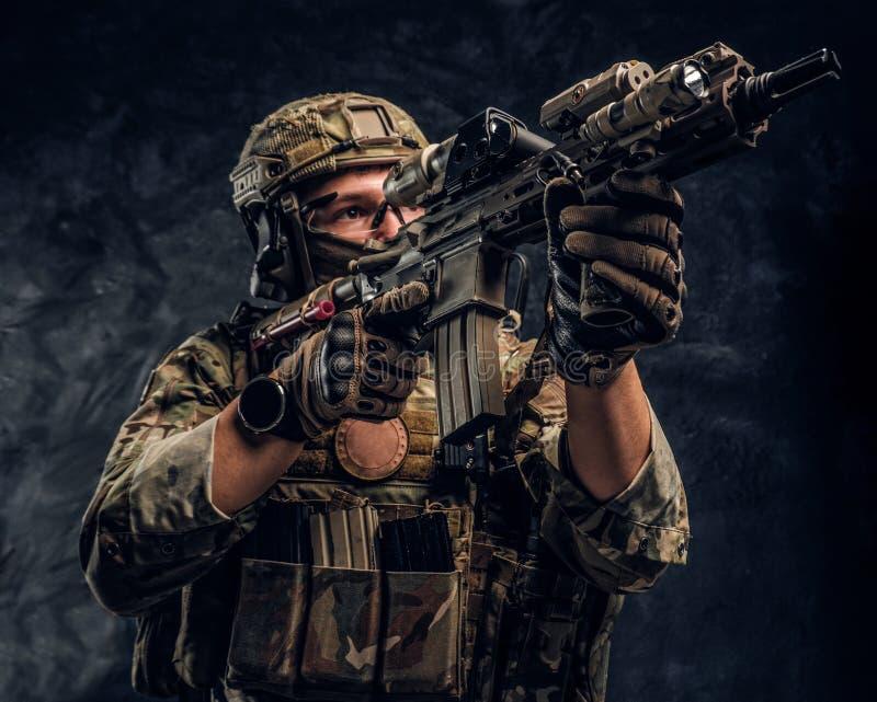 L'unité d'élite, soldat de forces spéciales dans l'uniforme de camouflage tenant un fusil d'assaut avec un laser aperçoivent et v photos libres de droits