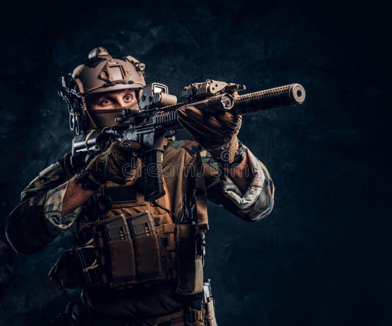 L'unité d'élite, soldat de forces spéciales dans l'uniforme de camouflage tenant un fusil d'assaut avec un laser aperçoivent et v photo stock