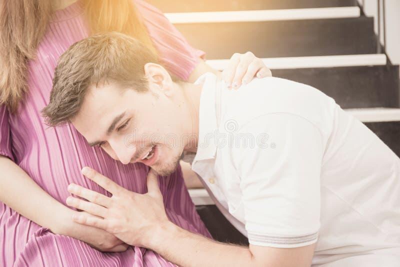 L'uomo è ascolta incinto della moglie, il padre bello asiatico ciao immagini stock