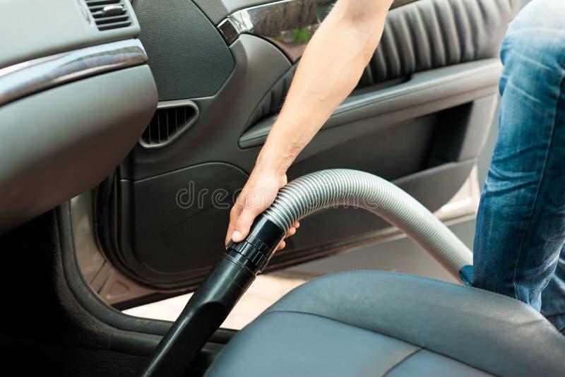 L'uomo è hoovering o pulente l'automobile immagine stock