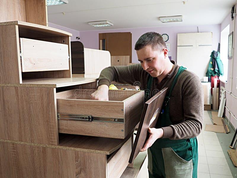 L'uomo è impegnato nel montaggio della mobilia fotografia stock libera da diritti