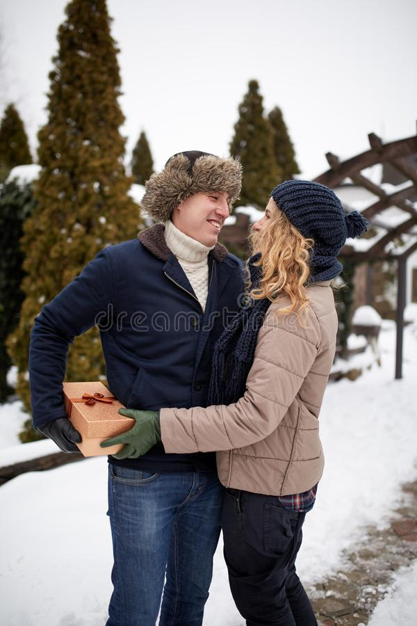 L'uomo è scatola dei pellami dietro il suo parte posteriore ed andando dare alla sua donna un presente il giorno, il Natale o il  immagini stock