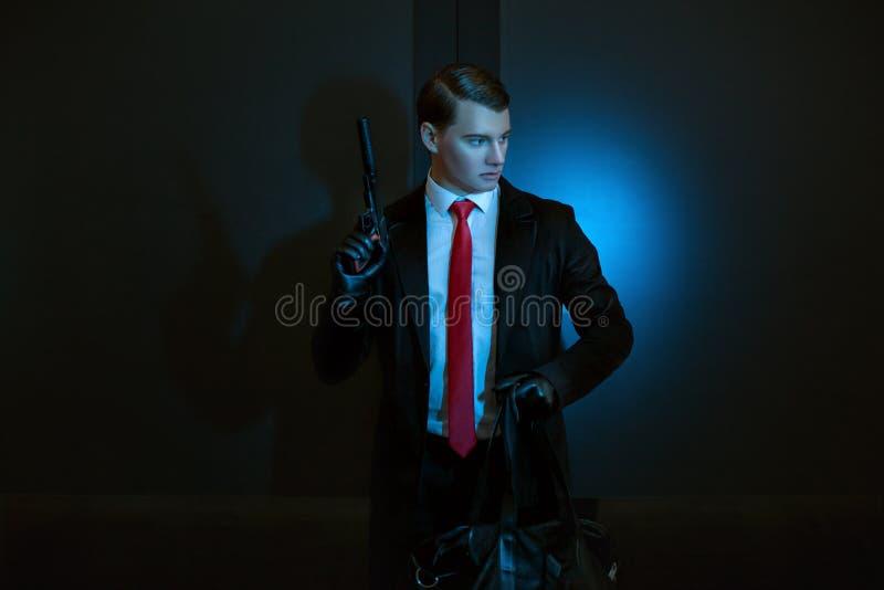 L'uomo è un assassino con una pistola in sua mano fotografia stock libera da diritti