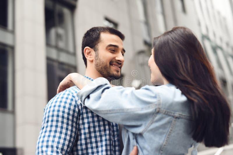 L'uomo abbraccia la ragazza su fondo di costruzione immagine stock libera da diritti
