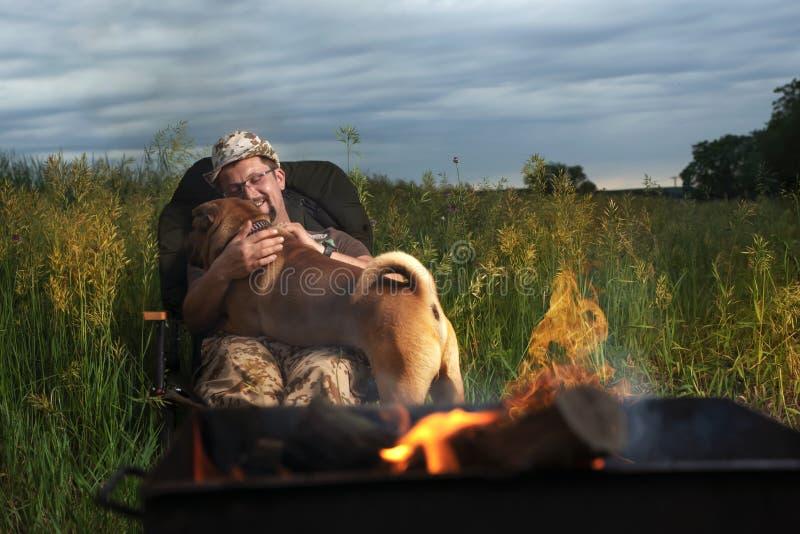 L'uomo abbraccia un cane di Shar Pei sulla natura sotto il cielo aperto alla luce di fuoco fotografie stock
