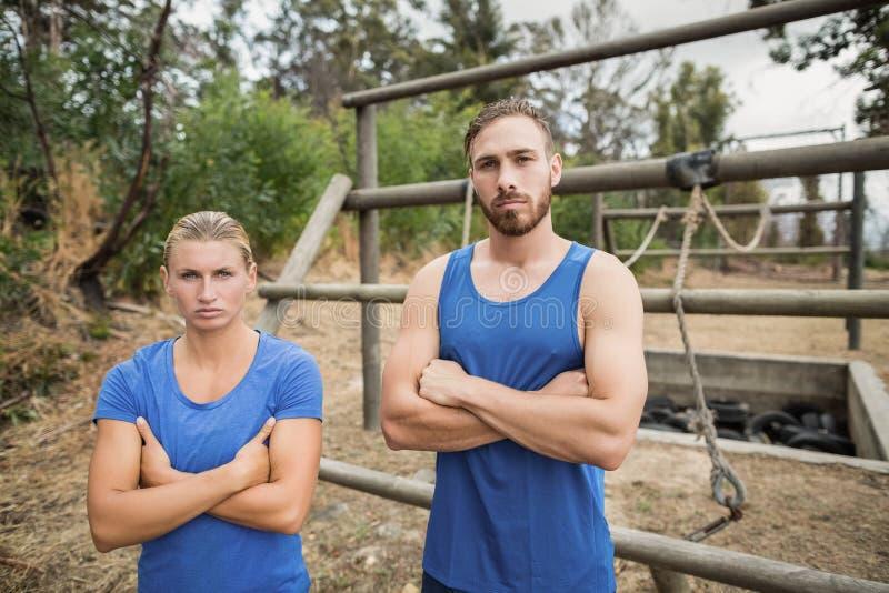 L'uomo adatto e la donna che stanno con le armi hanno attraversato durante l'addestramento di campo di addestramento immagine stock