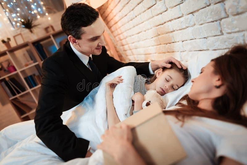 L'uomo adulto è messo per inserire la piccola figlia per dormire La figlia sta dormendo accanto a sua madre a letto immagine stock libera da diritti