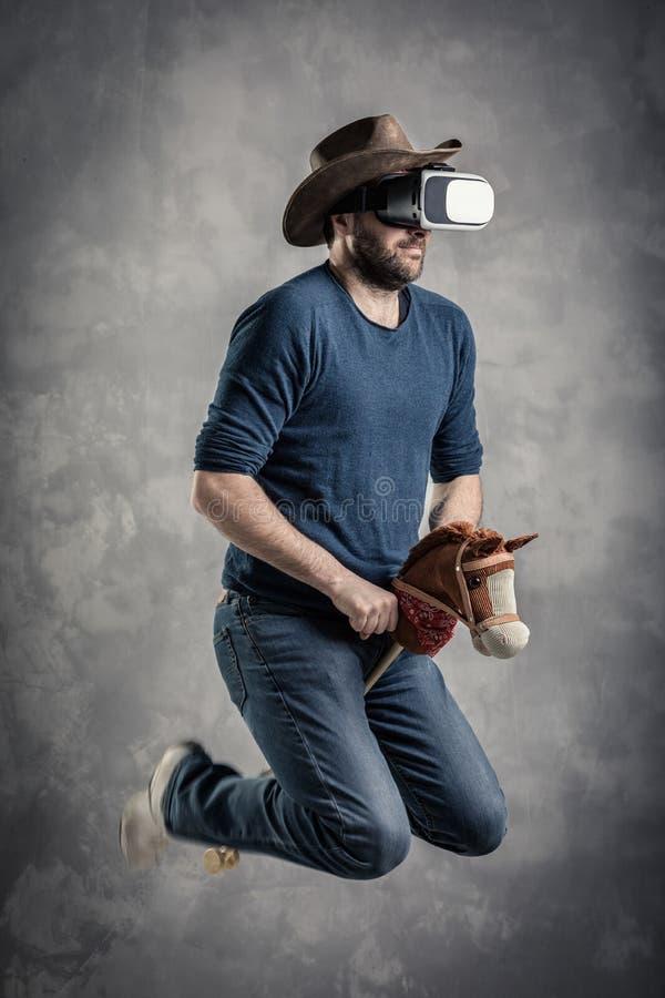 L'uomo adulto caucasico gode di di avvertire la simulazione immersive del gioco del cowboy di realtà virtuale Concetto del ritrat fotografia stock libera da diritti