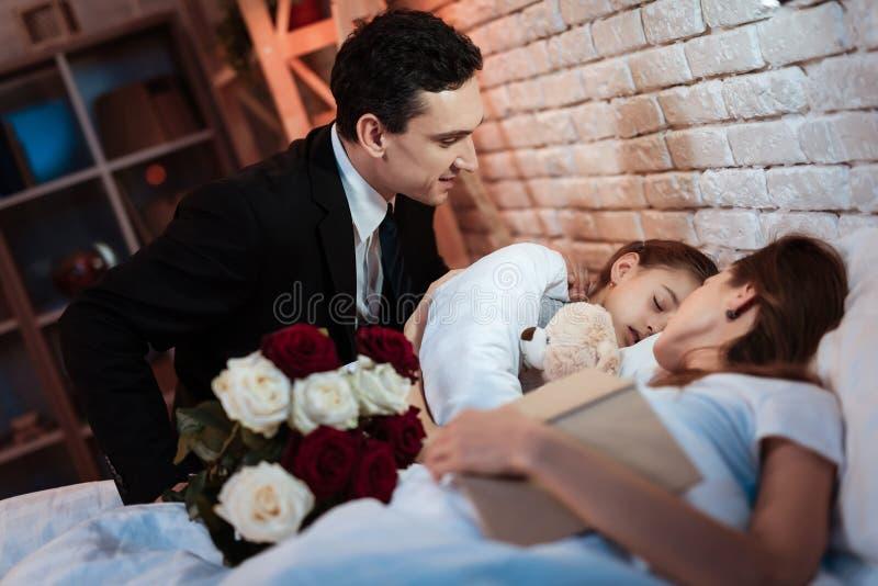 L'uomo adulto con il mazzo delle rose è messo per inserire la bambina per dormire Il bambino sta dormendo immagini stock