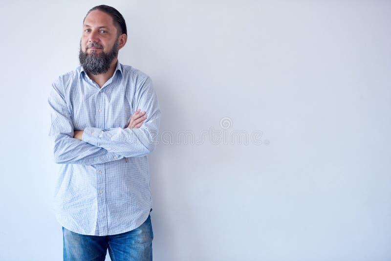 L'uomo adulto maturo che sorride con le armi ha attraversato contro la parete bianca immagine stock