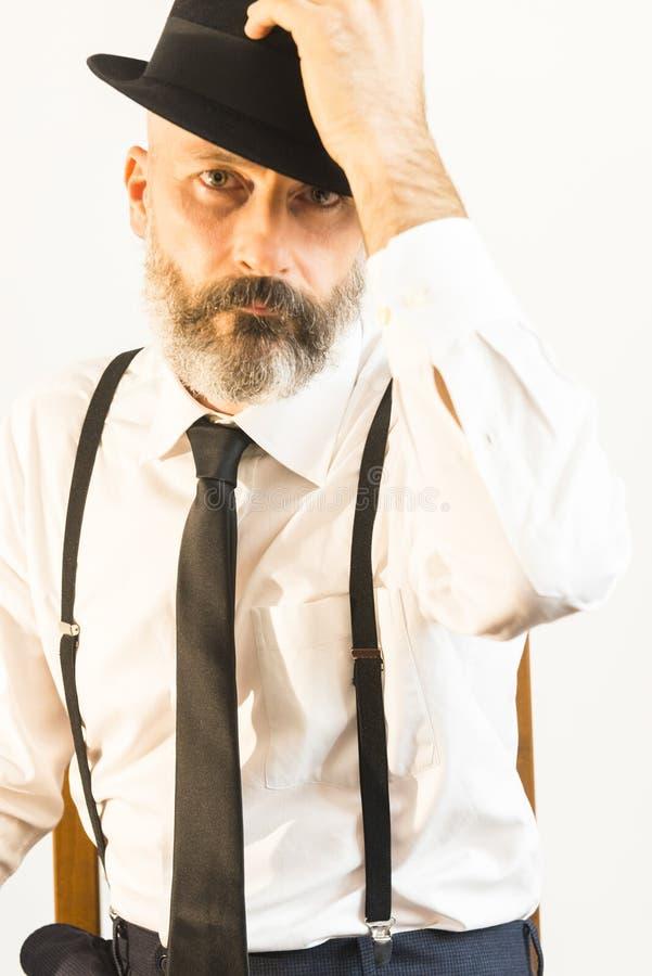 L'uomo adulto prende il suo cappello con la mano sinistra immagine stock