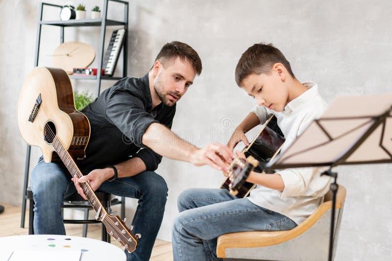 L'uomo adulto spiega il figlio, che impara a suonare la chitarra, a suonare correttamente l'accordo studiato Istruzione con la fa fotografia stock